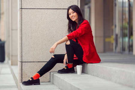 lovely businesswoman: Happy asian businesswoman smiling in the city. Happy lovely and beautiful mixed race Asian Caucasian young woman in casual red suite outdoor sitting on steps of building with coffee cup. Next generation