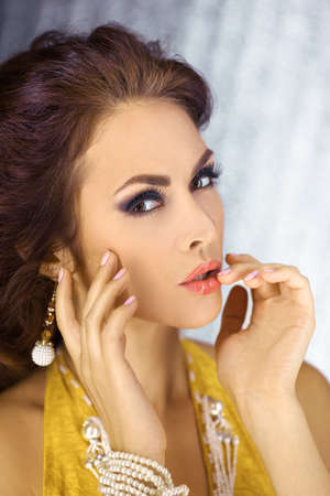 Beautiful woman with evening make-up and curly hair and yellow dress with jewelry pearls close-up. Smoky eyes. Fashion portrait photo with hands pointing to lips. Picture taken in the studio over bokeh shiny circles background. Stock Photo