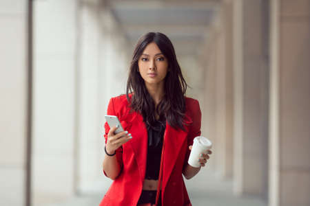 Young Asian woman with smartphone standing against street blurred building background and looking. Fashion business photo of beautiful girl in red casual suite with phone and cup of coffee Banco de Imagens
