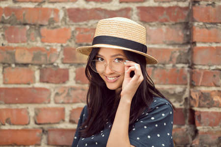 Asian student girl. Beautiful woman holding glasses against brick wall background. Mixed race student girl on university college campus park smiling happy and looking at camera. Archivio Fotografico