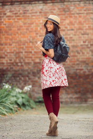 Asian student girl back to school university. Beautiful woman holding straps of backpack in brick wall background. Mixed race student girl on university college campus park smiling happy and looking at camera. Archivio Fotografico