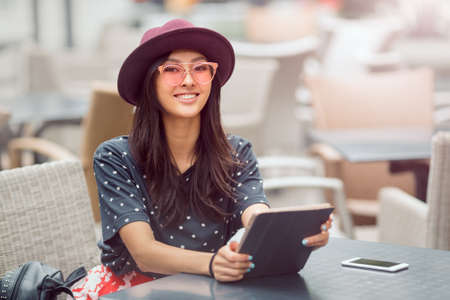Woman using tablet on lunch break in city cafe outdoors. Portrait of young smiling girl sitting with tablet pc and smartphone and looking at camera Stock Photo