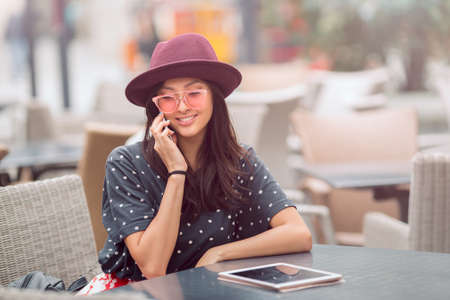 Woman talking by phone on lunch break in city cafe outdoors. Portrait of young smiling girl sitting with tablet pc and smartphone Stock Photo