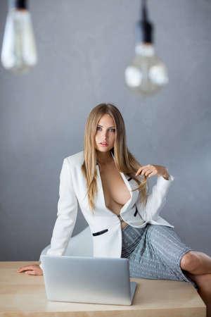 Bollen. Sexy zakenvrouw of secretaresse met notebook pc dragen witte pak met decollete grote borst zittend op tabler tegen exemplaar ruimte grijze muur achtergrond web camera chating surfen op internet te kijken naar de camera.