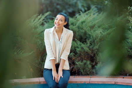 lovely businesswoman: Woman smiling - portrait of happy lovely and beautiful mixed race Asian Caucasian young businesswoman in casual clothes outdoor sitting in park Stock Photo