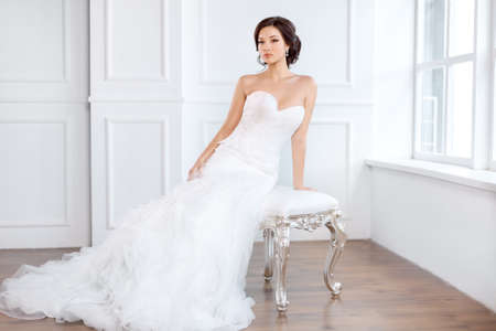 Bride in beautiful dress sitting on chair indoors in white studio interior like at home. Trendy wedding style shot in full length. Young attractive multi-racial Asian Caucasian model like a bride against big window tender looking.