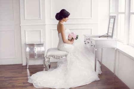 Huwelijksvoorbereiding. Mooie jonge bruid in witte trouwjurk binnen. Luxuty model kijken naar spiegel zitten op stoel met bruids boeket zoals thuis in de studio kamer met groot raam. Meisje toont trouw mode in gedecoreerd helder chic interieur, hoog