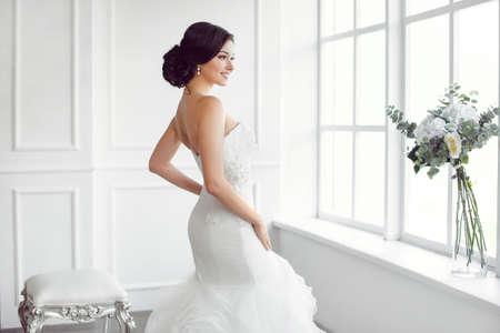 Portret van de schoonheid van de bruid draagt ??mode trouwjurk met veren met luxe vreugde make-up en kapsel, studio indoor foto. Jonge aantrekkelijke multiraciale Aziatische Kaukasische model. Ernstige sensuele mooie jonge vrouw als een bruid in witte ruimte bij b Stockfoto