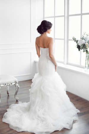 Beautiful bride looking at window. Studio shot in white room from behind. Young gorgeous model in brides dress in full length
