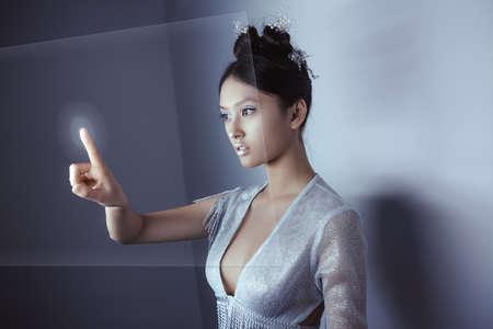 デジタル ホログラム スクリーンに触れる若いかなりアジアの女性。将来女性のコンセプト アート。ファッションの未来的な若い未来化粧室内で魅力的な多民族アジア白人モデルします。テキストのスペースにコピーします。
