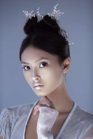 Portrait of futuristic young woman. Beautiful young multi-racial Asian Caucasian model cyber girl in silver urban clothes with conceptual hairstyle and make-up against blue copy-space background looking at camera. Sci-fi poster style.