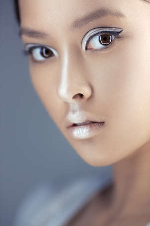 Portrait of futuristic young woman close-up. Beautiful young multi-racial Asian Caucasian model cyber girl in silver urban clothes with conceptual hairstyle and make-up against blue copy-space background looking at camera. Sci-fi poster style.
