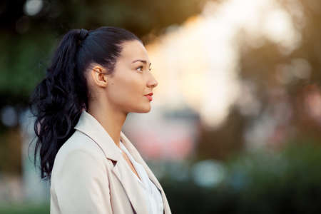 lovely businesswoman: Woman smiling - side view portrait of happy lovely and beautiful mixed race asian caucasian young businesswoman in casual clothes outdoor in the city park Stock Photo