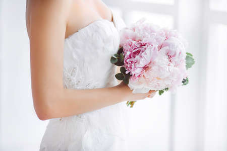 Bridal bouquet Beautiful of pink wedding flowers in hands of the bride. Close-up interior studio shot against white background