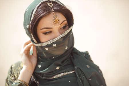 Retrato de la mujer árabe hermosa al aire libre. joven hindú. Retrato de la belleza modelo indio con el maquillaje brillante que oculta su cara detrás del velo de pie sobre el fondo de oro del desierto. Foto de archivo - 71277868