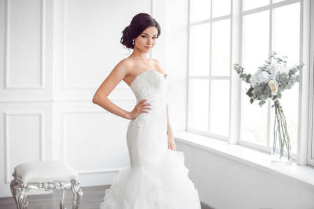 Beauty portrait of bride wearing fashion wedding dress with feathers with luxury delight make-up and hairstyle, studio indoor photo. Young attractive multi-racial Asian Caucasian model. Serious sensual beautiful young woman like a bride in white room at b