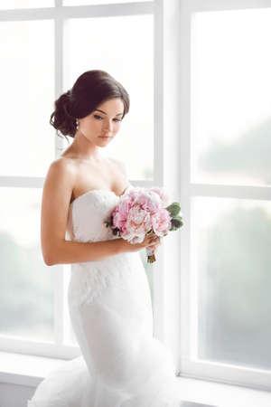 Mooie bruid. Bruiloft kapsel make-up luxe mode jurk en een boeket bloemen. Jonge aantrekkelijke multiraciale Aziatische Kaukasische model als een bruid tegen de witte kamer met groot raam tender naar beneden te kijken. Zijaanzicht