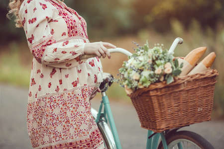 Pregnant belly against nature close-up. Pregnant girl retro French style with bicycle on a forest road. Beautiful pregnancy concept. Blonde happy woman with curly hair on nature background. Archivio Fotografico