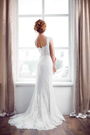 full lenght: Wedding. Beautiful bride indoors against big window in full lenght back view