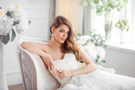 Boda. Novia en el hermoso vestido sentado en el sofá en interiores en el interior del estudio blanco como en casa. Disparo de estilo de moda de la boda. Joven atractiva morena caucásica modelo como una novia contra la ventana grande posando. Foto de archivo - 71575929