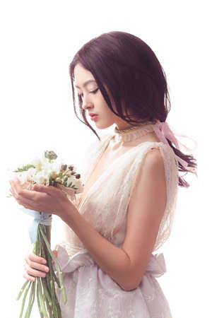 明るい背景に手で花牡丹とレースのホワイト ドレスで美しい少女。うれしそうなアジアの女性のモデルは春の花の花束とスタジオでポーズをとるし 写真素材