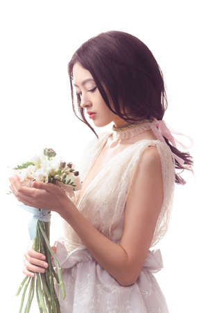 Beautiful girl in the lacy white dress with flowers peonies in hands on a light background. Joyful Asian female model posing in studio with bouquet of spring flowers.
