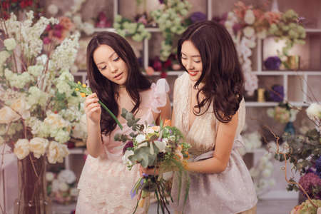 making dresses: Beautiful asian florist girls making bouquet of flowers for sale against floral bokeh background in flower shop indoors. Two attractive asian females florists working in retail store. 2 playful fashion models in tender dresses posing playing with flowers.