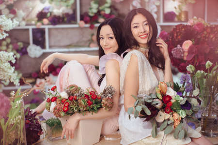 making dresses: Fashion models in tender dresses posing and looking at camera. Beautiful asian florist girls making bouquet of flowers on table for sale against floral bokeh background in flower shop indoors. Two attractive asian females florists working in store. Stock Photo