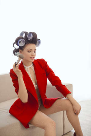 Model applying makeup. Woman in hair curlers applying dry cosmetic tonal foundation on the face using makeup brush indoors at home. Fashion model in red suit and shoes sitting on sofa
