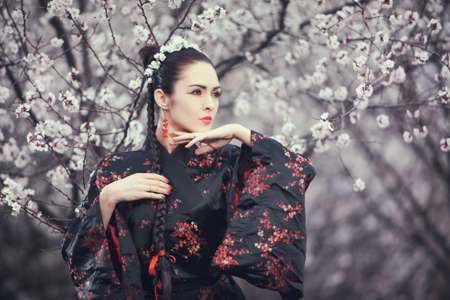ethnic woman: Attractive asian woman wearing kimono standing in blossoming garden. Gorgeous creative portrait outdoor on the nature. Girl looking away