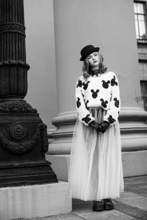 Woman in black and white clothes. Stylish retro urban girl trendy new age look. Accessories hat and Gloves. Fashion model posing in city stree. Photography portfolio. Stock Photo
