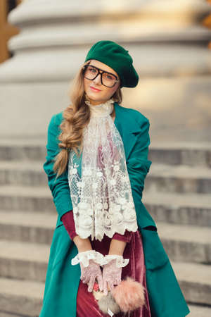 advertizing: Fashion shot. Happy smiling student girl back to school university photo. Beautiful woman posing at campus of univercity. Young teen model in hat and glasses with notebook in trendy clothes