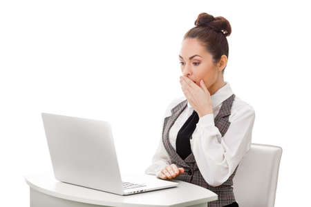 Image of young employer looking at laptop with surprise in office. Business and office concept surprised businesswoman using her laptop computer. Woman looking at pc screen against isolated white background Banco de Imagens