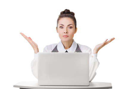 Confused businesswoman at work with laptop shrugging shoulders over white isolated background. Woman in question gesture looking at camera Stock Photo