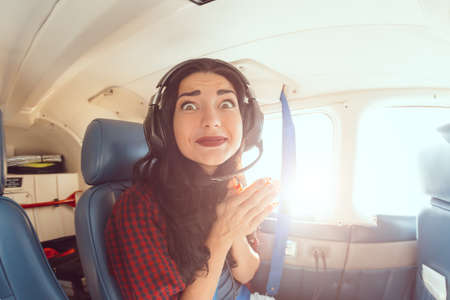 Fear of flying woman in plane . Person in airplane with aerophobia scared of flying being afraid while sitting in airplane seat. Funny girl portrain on fish eye lense Archivio Fotografico