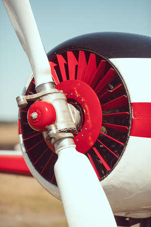 private club: Sport airplane red and white propeller closeup outdoors on the meadow Stock Photo