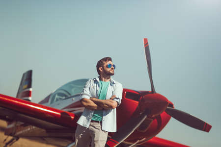 airstrip: Pilot and airplane. Cheerful handsome young man pilot standing near small sport plane