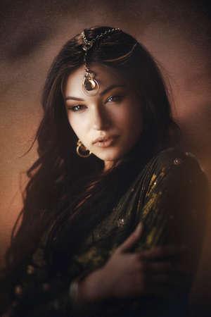 Egyptische prinses Cleopatra in de woestijn. Portret van een jonge vrouw met luxe make-up. Mooi meisje tegen de achtergrond van de woestijnzandstorm, jonge dame die modieuze gouden juwelen en kleding draagt.