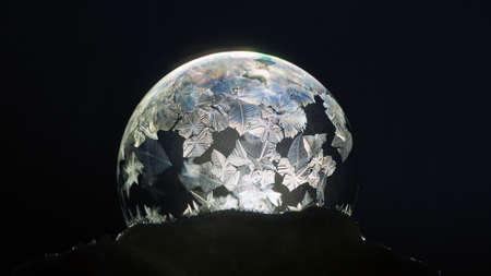 Fundo de inverno. Frozen soap bubble close-up. Para o cenário exclusivo de Natal e Ano Novo. Padrões de gelo brilhantes na bola de sabão contra o fundo preto. Foto de archivo - 79649646