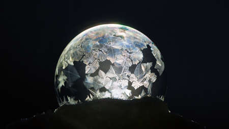 Winter background. Frozen soap bubble close-up. For Christmas and New Year Holidays exclusive backdrop. Shiny ice patterns on ball of soap against black background.