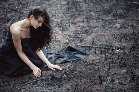 burned out: Sad girl sitting on the burned-out land. Concept of environmental disaster. Global problems with ecology. Young attractive multi-racial Asian Caucasian woman in black dress on nature Stock Photo