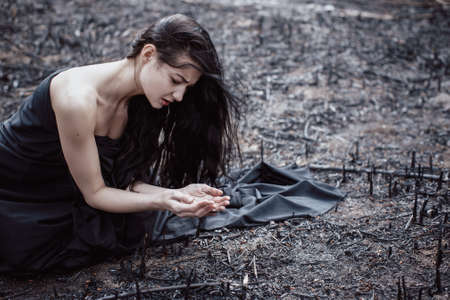 Sad girl sitting on the burned-out land. Concept of environmental disaster. Global problems with ecology. Young attractive multi-racial Asian Caucasian woman in black dress on nature Stock Photo
