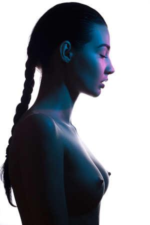 Kunst mode studio portret van naakt elegante vrouw met gesloten ogen op witte achtergrond. Profiel van aantrekkelijk gemengd ras Aziatische Kaukasische vrouwelijke model met vlecht. Perfect slank lichaam. Schoonheid en gezondheid. Gekleurde profashional lichten