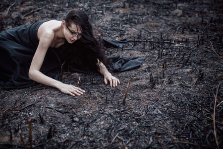 eradication: Sad girl sitting on the burned-out land. Concept of environmental disaster. Global problems with ecology. Young attractive multi-racial Asian Caucasian woman in black dress on nature Stock Photo