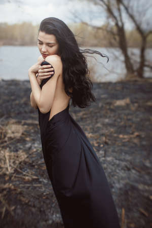 Sad girl standing on the burned-out land. Concept of environmental disaster. Global problems with ecology. Young attractive multi-racial Asian Caucasian woman in black dress on nature Stock Photo