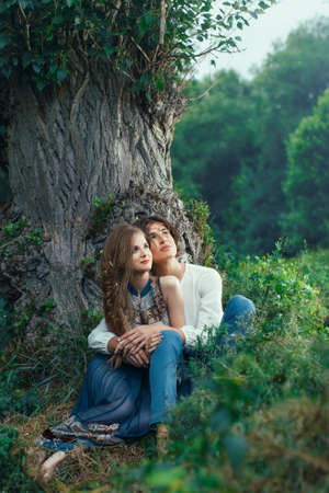Young couple of elves in love sitting in magical forest agaist the big tree outdoor on nature. Fairy tale of love, relationship and magik people concept. Man ambracing woman Foto de archivo