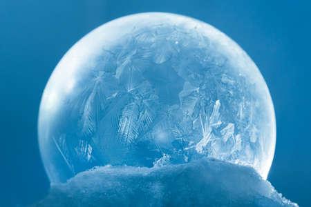 Gefrorener Schneekugelweihnachtsmagieball mit Fliegenschneeflocken. Winterhintergrund. Für Weihnachten und Neujahr Urlaub kostbare Kulisse. Eismuster bereiften auf Seifenbausch gegen blauen abstrakten bokeh Hintergrund.