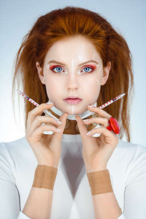 Beautiful Woman before Plastic Surgery Operation Cosmetology. Beauty Portrait Fashion Concept. Treatment with botox or hyaluronic collagen injection. Young red hair girl holding syringes in hands with correction mark for plastic surgery on her serious face. Studio shoot agaisnt blue background