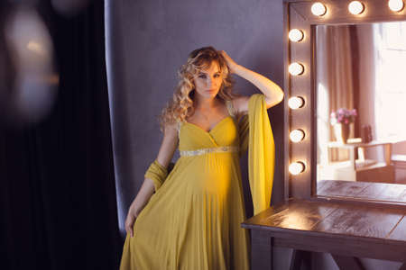 portait: Pregnant woman. Romantic portait photo of beautiful blonde girl posing in sexy evening dress looking away at home. Indoor shot against gray wall and mirror. Stock Photo