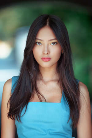 Woman portrait. Sensual lovely and beautiful mixed race asian caucasian young girl looking at camera outdoor against green blurred bokeh background. Gorgeous slim model posing outside Stock Photo